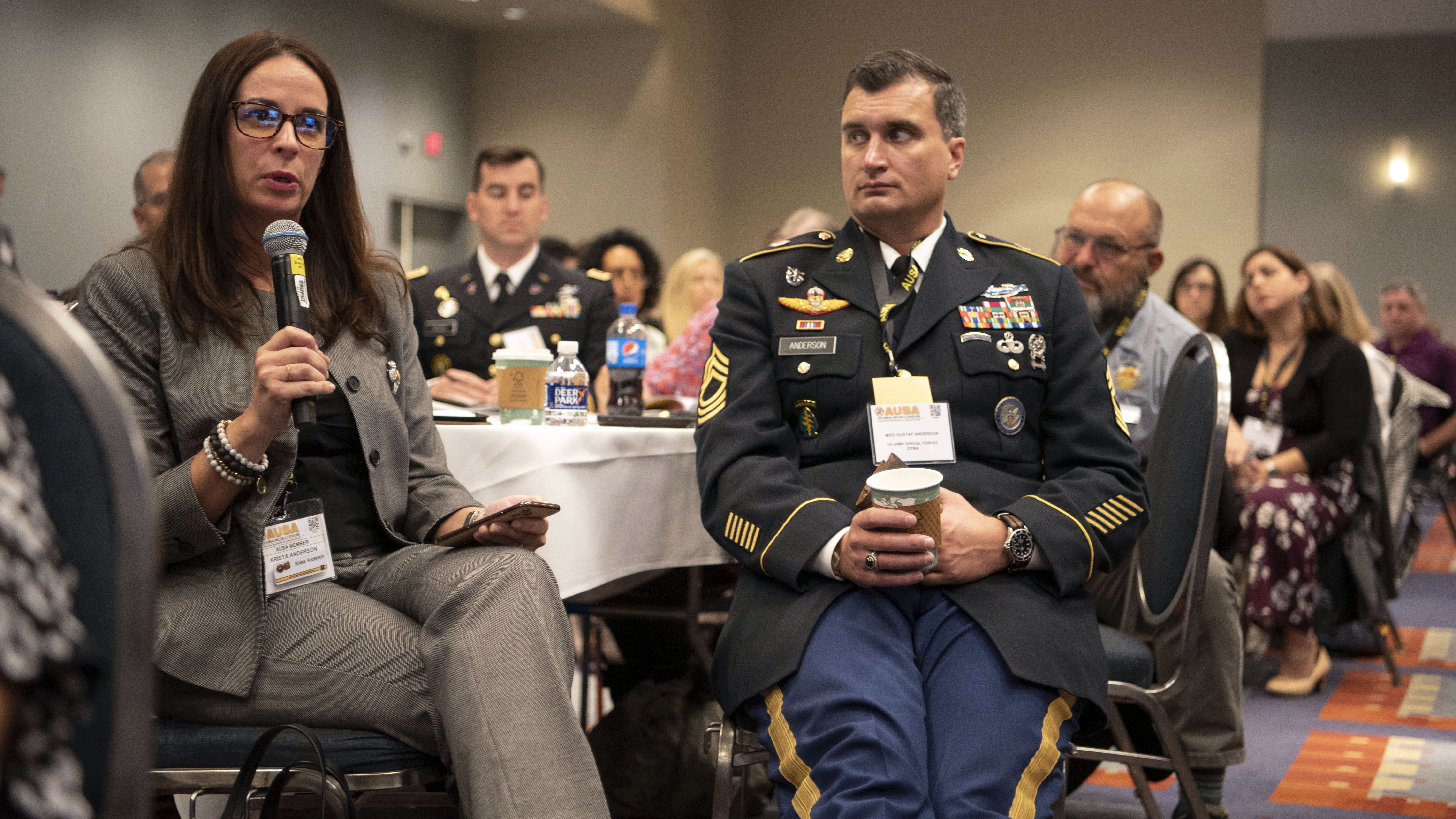 With her husband, MSG Gustav Anderson by her side, Krista Anderson asks a question to the panel at the Family Forum II: Army Housing and PCS at the 2019 AUSA Annual Meeting and Exposition at the Washington Convention Center on Oct. 15, 2019.