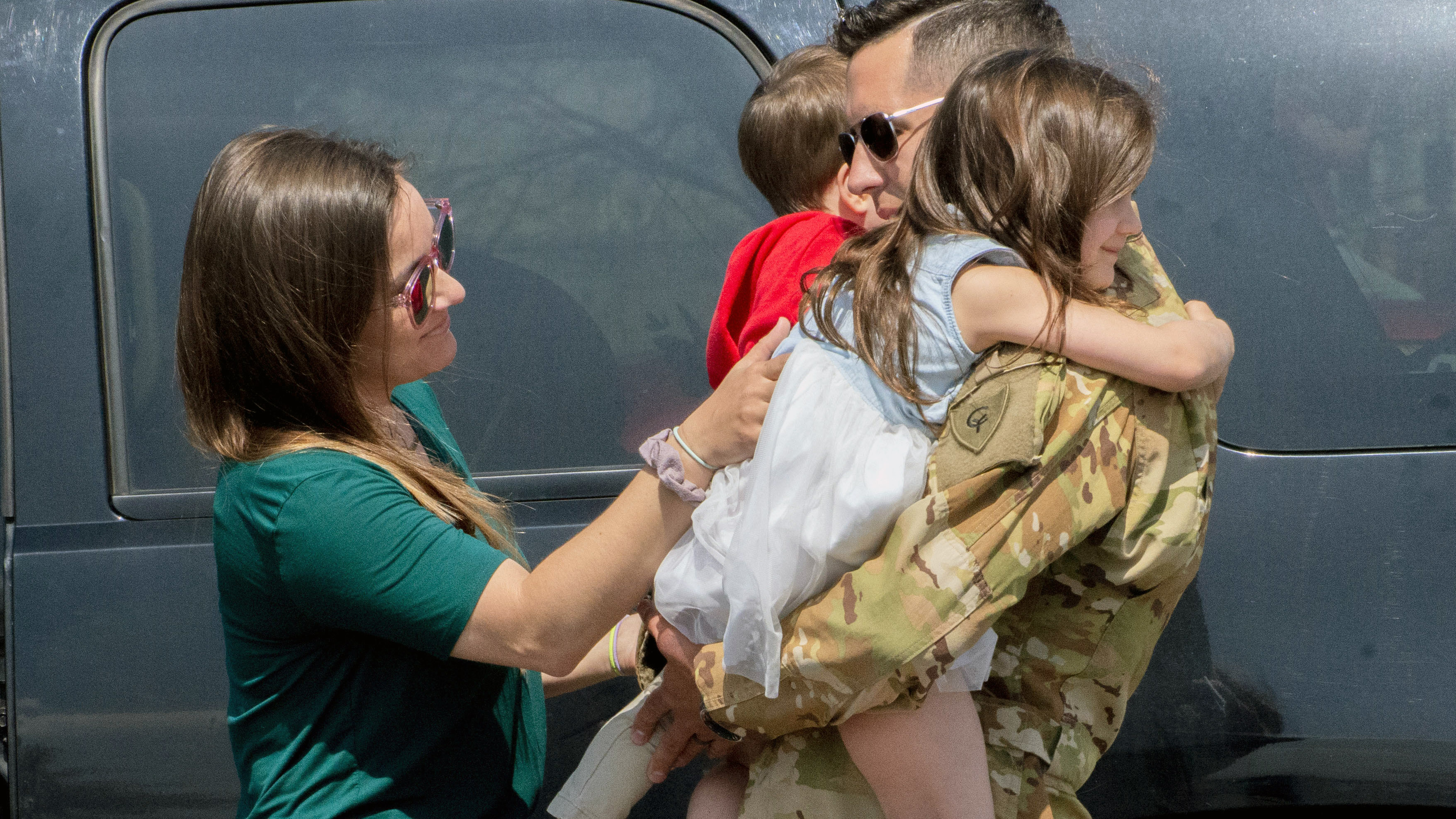 Soldier hugging family