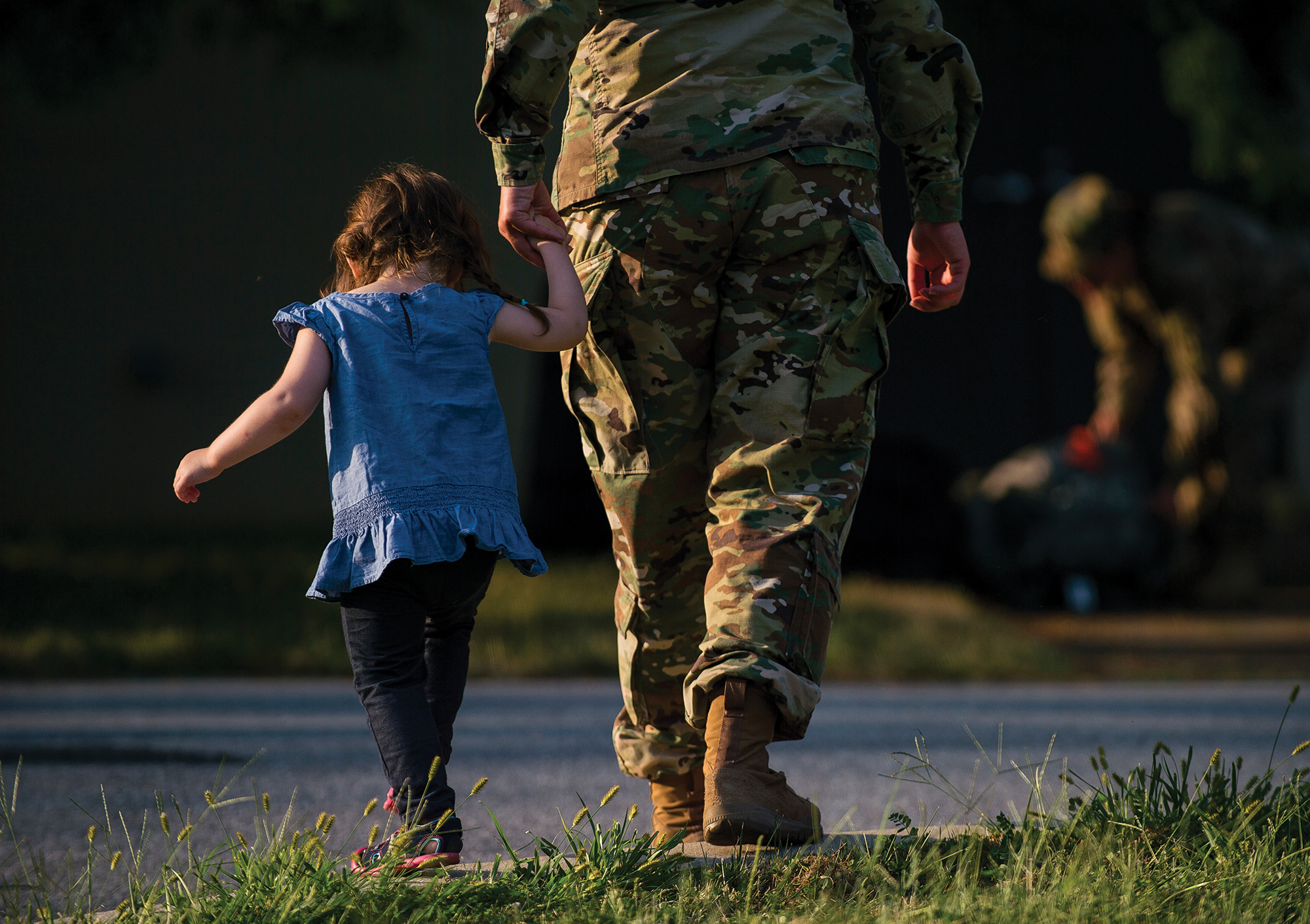 Little girl holding hand of military parent