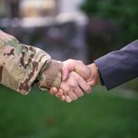 Soldier shaking hands with businessman.